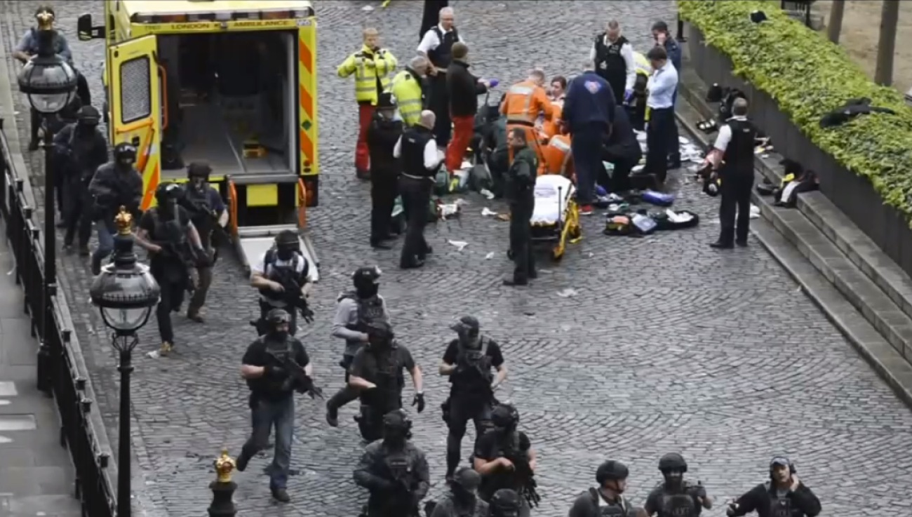 Special Forces moving in as ambulance crew in the background trying to save the life of the police officer who was stabbed by the terrorist.